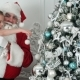 Fake Santa Claus Decorating a Christmas Tree Holding a Little Girl in His Arm