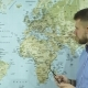 a Young Businessman Takes Off His Glasses and Examines a Geographical Map