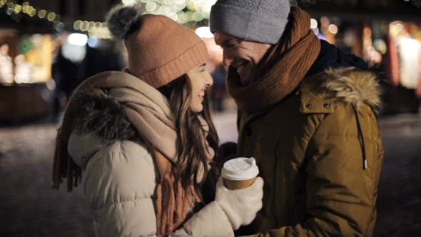 Happy Couple with Coffee Outdoors on Christmas