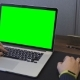 Man's Hands on the Table with Green Screen Laptop