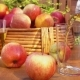 Apple Juice and a Basket of Ripe Apples on a Wooden Table