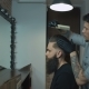 Unequaled Barber with a Beard and a Tattoo Is Drying the Hair of His Client in a Blue Cutting Hair