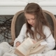 Cute Little Girl Sitting in a Christmas Chair and Going Through a Book