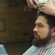 Young Bearded Man Getting Haircut By Hairdresser While Sitting in Chair at Barbershop