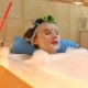 Beautiful Brunette Woman Wearing Cosmetic Face Mask Relaxes in Foamy Bath