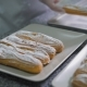 Baker By Hands Neatly Folded Freshly Baked Eclairs with Sugar Powder on a Beautiful White Plates