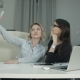 Two Female Colleagues Taking Selfie with Phone in the Office