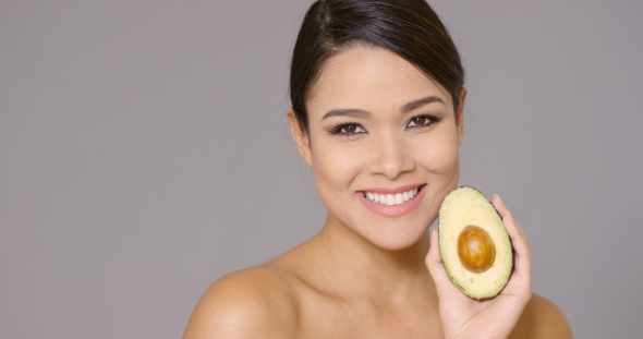 VideoHive Smiling Happy Woman Holding a Ripe Avocado Pear 19263042