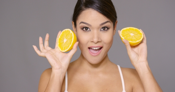 VideoHive Cute Young Woman Holding a Halved Fresh Orange 19263048