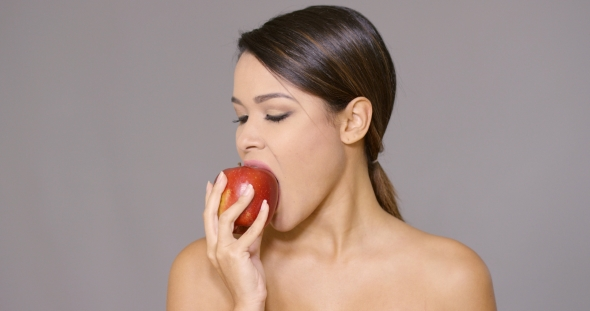 VideoHive Young Woman Biting Into a Fresh Red Apple 19263164