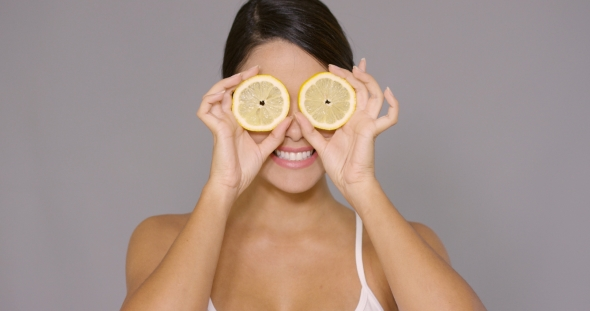 VideoHive Smiling Young Woman Holding Lemons To Her Eyes 19263173