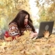 Woman with Laptop in the Autumn Park