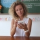 Young Blonde Woman Using Smartphone in Cafe