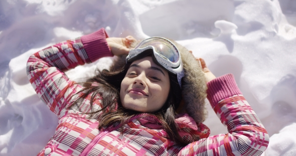 VideoHive Young Woman Lying on Snow with Ski Goggles 19274541
