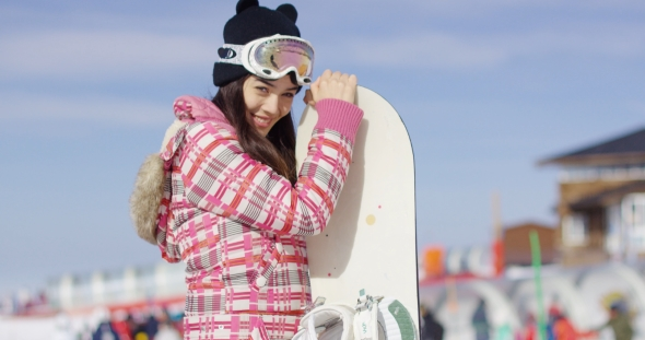 VideoHive Cute Asian Female Snowboarder Relaxing on Slope 19274561