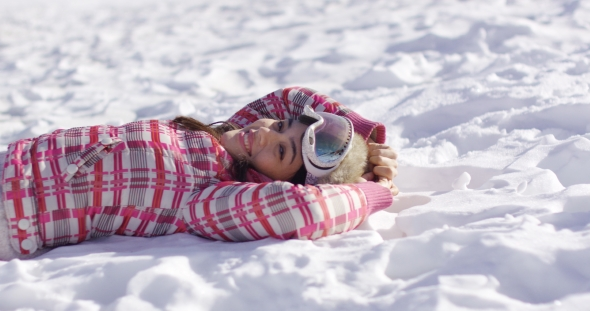 VideoHive Young Woman Lying on Snow with Ski Goggles 19274687