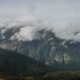 of High Snowly Mountains with Clouds and Spruce Forest