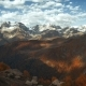of Golden Mountain Hills, Snow Tops and Red Forest. Cloud Shadows Show Relief