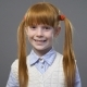 Cute Ginger Girl with Two Pigtails Looking Onto the Camera