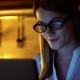Beautiful Attractive Woman in Glasses Browsing Internet on Laptop. Evening Kitchen.