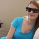 Young Beautiful Woman Sitting on a Couch in 3D-glasses. Switches on Smart TV and Watches 3d Movie