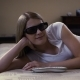 Beautiful Young Woman Lying on a Couch. Puts on 3D-glasses Switches on Smart TV and Watches 3d Movie