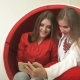 Two Women Sitting in Red Chair, Making Selfies