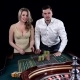 Young Couple Celebrating Win at Roulette Table in Casino. Black