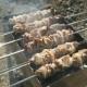 Cooking of Pork Skewers on Metal Skewers on Coals