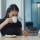 Beautiful Girl Drinking Coffee and Using Phone in a Cafe