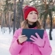 Young Woman Looking for the Right Way, Using a Tablet or a GPS Navigator. M in the Snowy Winter