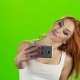 On the Smartphone Camera Redhead Girl Doing Selfie. Green Screen