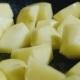 Diced Potatoes Fried in a Pan. Under It Boils Sunflower Oil. Junk Food