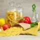 Raw Pasta, Cheese, Olive Oil and Fresh Vegetables on Gray Background