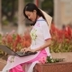 The Beautiful Asian Girl Speaks on a Laptop on the Street and a Beautiful National Dress Ao Dai with