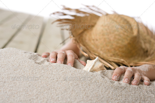 Naked Woman Sunbathing On Beach With Straw Hat Lying Down