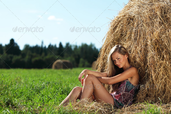 girl next to a stack of hay - Stock Photo - Images