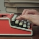 Man's Hands Typing on a Red Typewriter