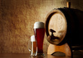 Beer into glass on a old stone and old barrel - PhotoDune Item for Sale