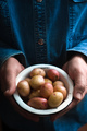 Hands with raw potatoes in the metal bowl
