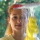 Young Attractive Woman Washes a Window Using a Special Brush. Dolly Shot.