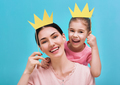 Mom and child are holding crown