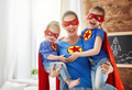 Girls and mom in Superhero costumes
