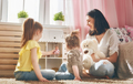 mother and daughters play with doll house
