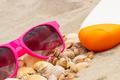 Seasonal concept, heap of shells, sunglasses and sun lotion