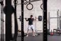 Man lifting heavy barbell on squat rack