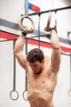 Muscular gymnast exercising on rings