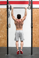 Rear view of muscular man hanging from rings