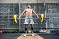 Strong man lifting heavy barbell