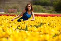 Romantic woman in flower field in sunny day